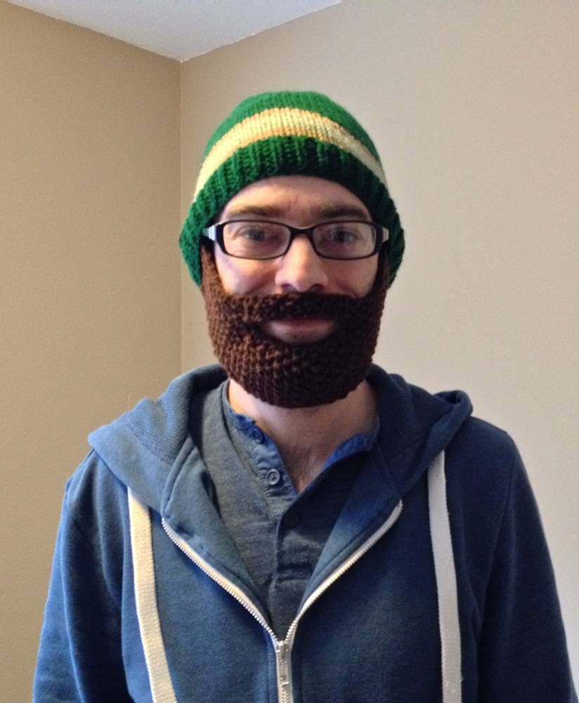 With Halloween coming up, I thought a knitted hat with a beard would be an excellent pattern to both protect you from the elements and add to a costume. This is a hat, just like the pattern provided last month, with a beard attachment.